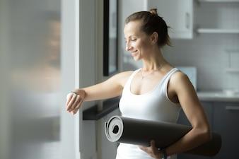 Mulher desportiva com uma esteira olhando para o relógio dela