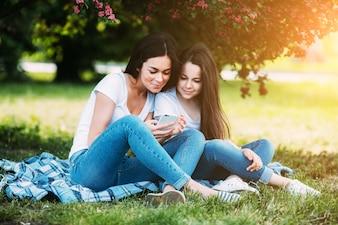 Mulher e menina sentadas sob uma árvore em flor