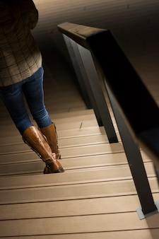 Mulher em botas de couro descendo as escadas