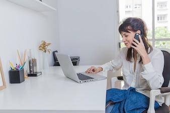 Mulher em casa com laptop falando ao telefone