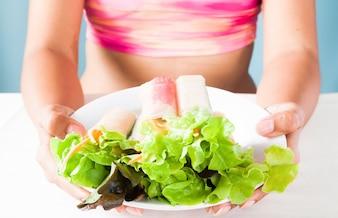 Mulher em sutiã de esporte segurando prato de salada após treino de fitness no dia de verão. Conceito de alimentação saudável