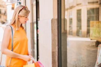 Mulher em vestido amarelo olhando a janela da loja