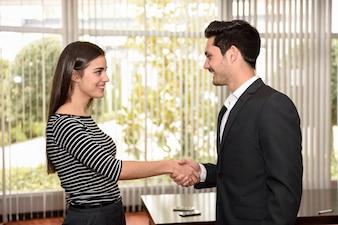 Mulher feliz apertando as mãos com seu empregador depois de uma entrevista de emprego