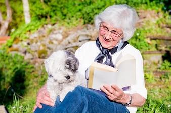 Mulher feliz que lê com seu cão