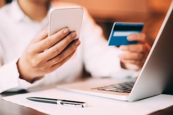 Mulher gerente de smartphones de compras de crédito
