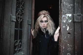 Mulher gótica assustadora na entrada da porta