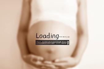 """Mulher gravida com um cartaz """"carregamento"""""""