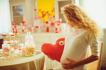 Mulher gravida com um coração de pelúcia