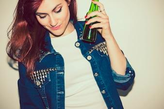Mulher legal dançando com uma garrafa de cerveja