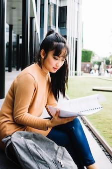 Mulher lendo caderno fora