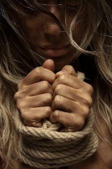 Mulher loura com mãos amarradas