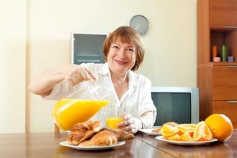 Mulher madura tomando café da manhã