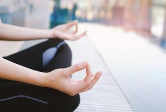 Mulher meditando na posição de lótus closeup na piscina ao ar livre com cópia espaço