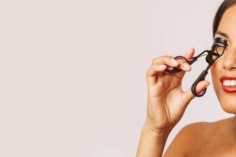 Mulher moderna usando o curl de cílios