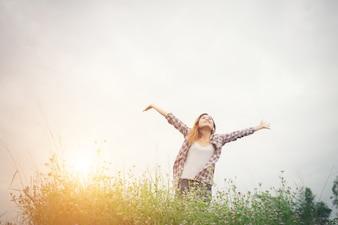 Mulher moderno bonita nova em um campo de flor ao pôr do sol. Freed