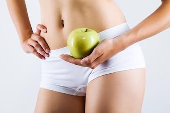 Mulher na roupa interior com uma maçã