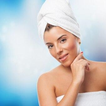 Mulher na toalha branca sobre fundo azul.
