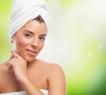 Mulher na toalha com a mão para o rosto