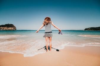 Mulher nas costas entrando para uma bela praia australiana.