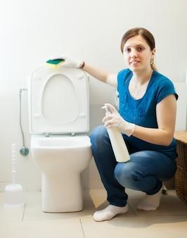 Mulher no banheiro com esponja e limpador