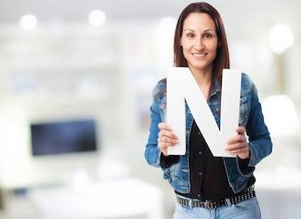 """Mulher no revestimento denim sorrindo com a letra """"n"""""""