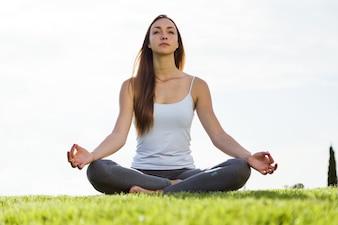 Mulher nova bonita que faz a ioga na rua.