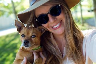 Mulher nova bonita que olha a câmera com seu cão.