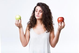 Mulher nova bonita que prende maçãs verdes e vermelhas sobre o fundo branco.