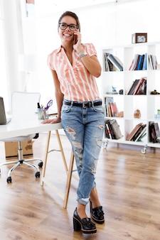Mulher nova bonita que trabalha com o telefone móvel em seu escritório.