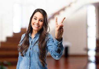 Mulher nova de sorriso que mostra o gesto da vitória