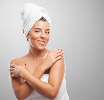 Mulher nova na toalha que toca em seus ombros