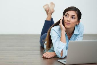 Mulher nova que convida o telefone e deitado no chão