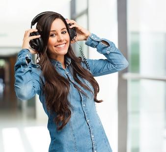 Mulher nova que escuta a música com um grande sorriso