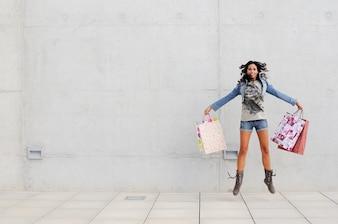 Mulher nova que salta com os sacos de compras