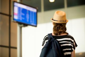 Mulher olhando telas no aeroporto