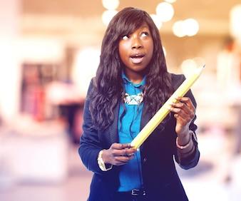 Mulher pensativa com um lápis gigante