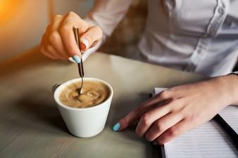 Mulher que agita o café com uma colher de chá