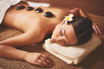 Mulher que aprecia uma massagem com pedras