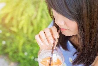 Mulher que bebe de uma bebida de laranja
