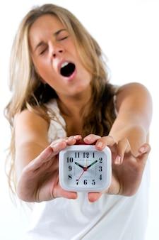 Mulher que boceja mostrando relógio