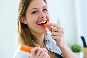 Mulher que come a cenoura