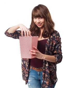 Mulher que come a pipoca de um pacote de popcornwoman comendo pipoca de um pacote de pipoca