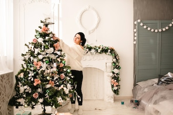 Mulher que decora uma árvore de Natal