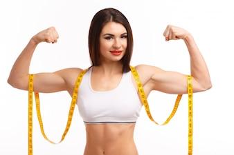 Mulher que espreme a ambos os bíceps e uma fita métrica