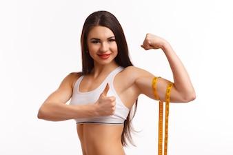 Mulher que espreme o bíceps