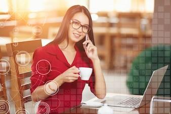 Mulher que fala no telefone com uma chávena de café