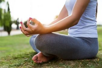 Mulher que faz a ioga em um parque