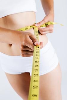 Mulher que mede seu corpo magro. Isolado no fundo branco.