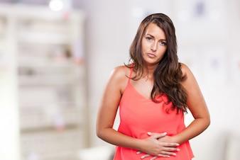 Mulher que tem uma dor de estômago