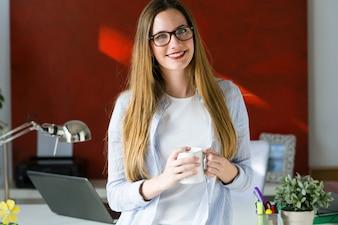Mulher que trabalha com uma xícara de café em suas mãos